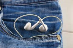 Coeur des écouteurs blancs - un symbole de l'amour piaule hors de la poche de pantalons de jeans Amour pour la musique Le concept Image libre de droits