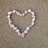 Coeur des cailloux marquetés sur un fond de sable Photographie stock libre de droits