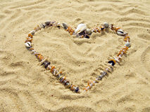 Coeur des coquilles de coque et des cailloux de mer Photographie stock