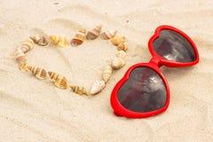 Coeur des coquilles et des lunettes de soleil sur le sable à la plage Photos libres de droits