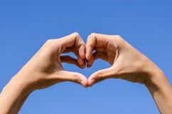 Coeur des doigts avec le ciel bleu Image libre de droits