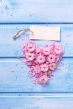 Coeur des fleurs et des pétales roses et Empty tag sur le bois bleu Photos libres de droits