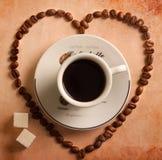 Coeur des grains de café autour de cuvette Photographie stock