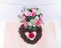 Coeur des grains de café avec des fleurs, étoiles de mer Photos stock