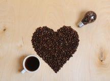 Coeur des grains de café, d'une tasse de café et d'une ampoule avec des grains de café à l'intérieur sous forme de flèche piercin Images stock