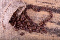 Coeur des grains de café en gros plan avec un sac à toile sur le te en bois Photographie stock libre de droits