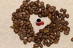 Coeur des grains de café et d'une tasse sur le fond de toile de jute Photos stock