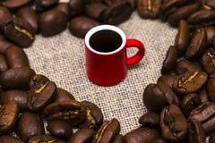 Coeur des grains de café et d'une tasse sur le fond de toile de jute Photo stock