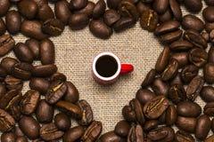 Coeur des grains de café et d'une tasse sur le fond de toile de jute Photos libres de droits