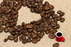 Coeur des grains de café et d'une tasse sur le fond de toile de jute Image libre de droits