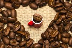 Coeur des grains de café et d'une tasse sur le fond de toile de jute Photographie stock