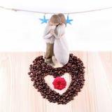 Coeur des grains de café et du concept d'amour de la poupée de couples avec l'écoulement Images stock