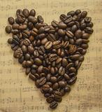 Coeur des grains de café sur la feuille de musique de fond Images stock