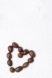 Coeur des grains de café sur le fond du sucre en poudre Image stock