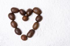 Coeur des grains de café sur le fond du sucre en poudre Photographie stock libre de droits