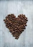 Coeur des grains de café sur le fond en bois Image libre de droits
