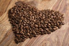 Coeur des grains de café sur le fond en bois Photo stock
