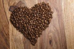 Coeur des grains de café sur le fond en bois Image stock