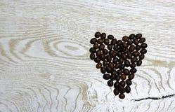 Coeur des grains de café sur le fond en bois clair Images libres de droits