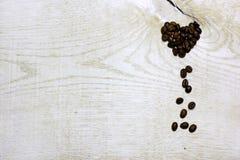 Coeur des grains de café sur le fond en bois clair Photographie stock libre de droits