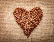 Coeur des grains de café sur le sac brun texturisé Image stock
