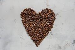 Coeur des grains de café sur un fond blanc Images stock