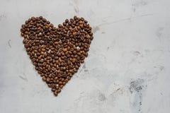 Coeur des grains de café sur un fond blanc Image stock