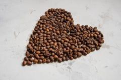 Coeur des grains de café sur un fond blanc Photographie stock
