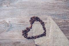 Coeur des grains de café sur un fond en bois Photo stock
