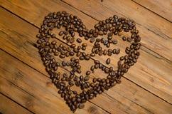 Coeur des grains de café sur une table en bois Image libre de droits