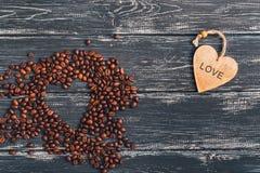 Coeur des grains de café sur une vieille surface foncée en bois Coeur en bois avec amour des textes Vue supérieure avec l'espace Image stock
