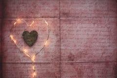 Coeur des lumières de Noël sur le fond rustique Images stock