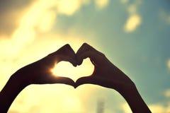 Coeur des mains contre le ciel au coucher du soleil Coeur dans le ciel Photo libre de droits