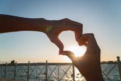 Coeur des mains femelles sur le fond de coucher du soleil Image stock