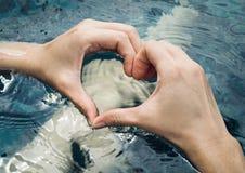 Coeur des mains sur la piscine Image stock