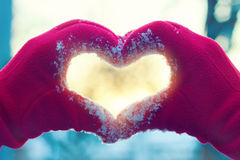 Coeur des mains sur le fond d'hiver Image stock