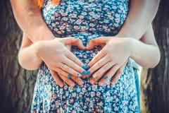 Coeur des mains sur le ventre d'une femme enceinte Images stock