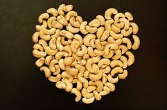 Coeur des noix de cajou sur le fond noir Photo stock