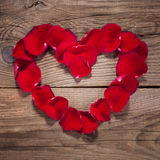 Coeur des pétales de rose sur les vieux conseils en bois image stock