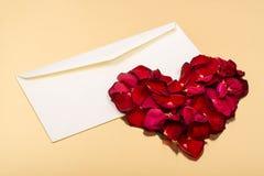 Coeur des pétales rouges se trouvant sur enveloppes vides ouvertes Photo stock