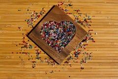 Coeur des perles colorées dans la boîte en forme de coeur en bois Photographie stock