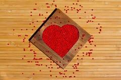 Coeur des perles rouges dans la boîte en forme de coeur en bois Photographie stock