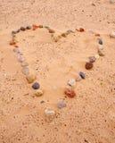 Coeur des pierres de mer sur le sable Images libres de droits