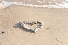 Coeur des pierres sur la plage de sable Amour conceptuel, fond de jour de valentines Mer baltique Image stock