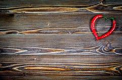 Coeur des poivrons de piment sur une surface en bois Photos stock