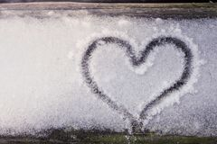 Coeur dessiné dans le bois qui a la neige là-dessus photographie stock libre de droits