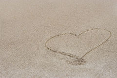 Coeur dessiné dans le sable Photos stock