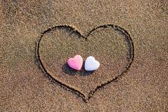 Coeur dessiné dans le sable avec deux coeurs Photographie stock libre de droits
