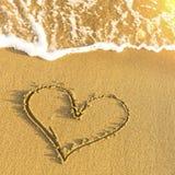 Coeur dessiné dans le sable de plage, la vague molle et l'éclat solaire Amour Photographie stock libre de droits