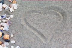Coeur dessiné dans le sable Seashell de feston sur le rose Photos stock